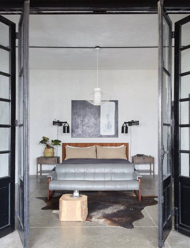 Spacious, industrial bedroom with leather sofa at foot of bed