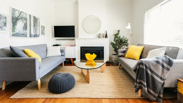 living room space with grey couches and white walls