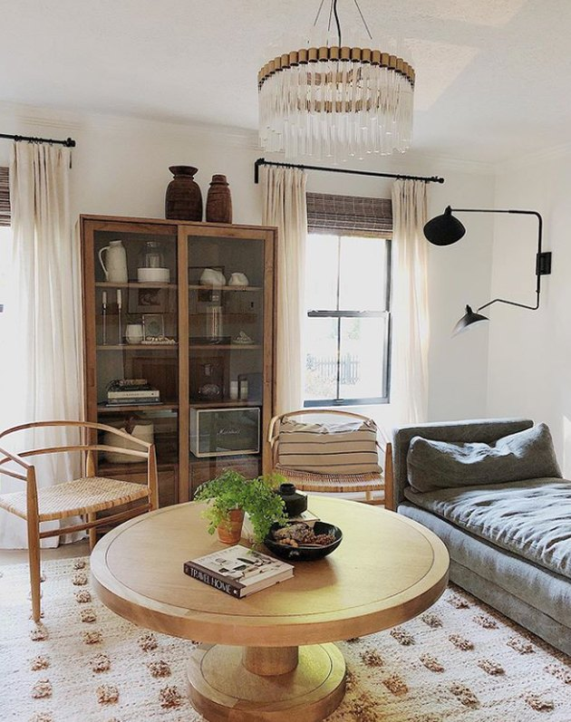 living room lighting idea with double arm sconce and Art Deco pendant