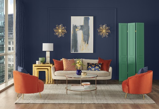 living room with navy walls and sofa and orange chairs