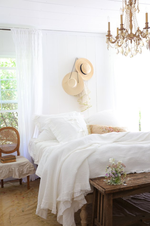 Crystal chandelier in French country bedroom with drapery at window and wooden bench at foot of the bed