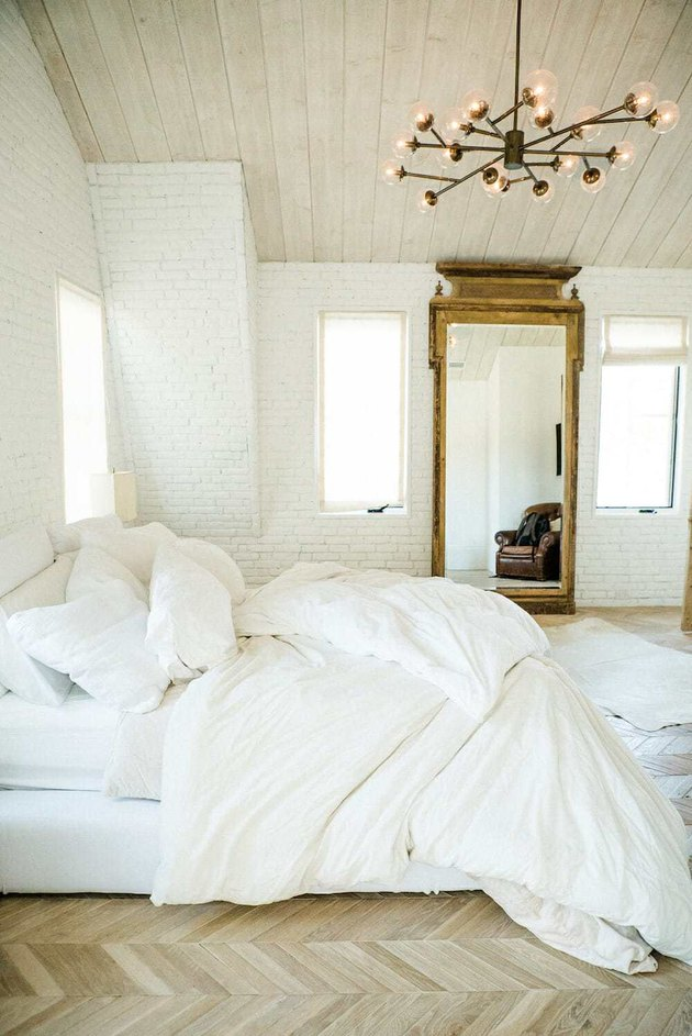 Scandinavian bedroom idea with all white room with chevron wood floors and white brick walls