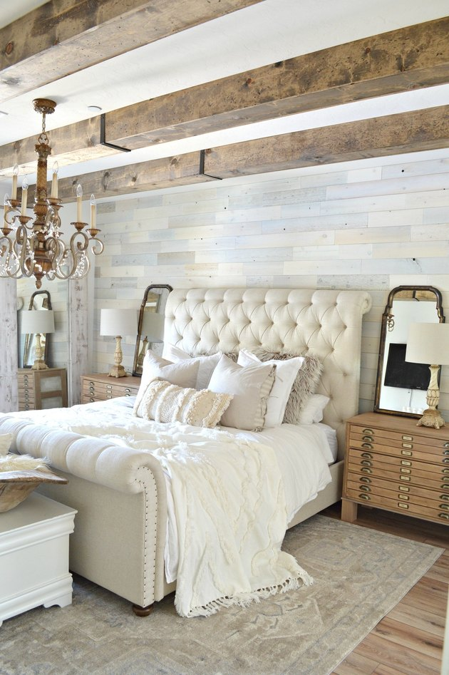 Soft textiles in French country bedroom with exposed wood beams and tufted headboard