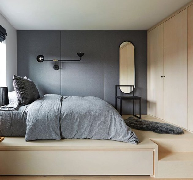 Scandinavian bedroom idea with bleached wood room and gray accents with upholstered wall panels and modern accents