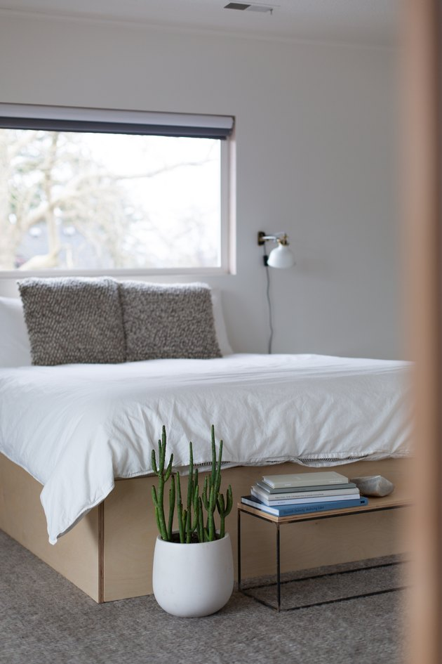 Bedroom with white bed and plant