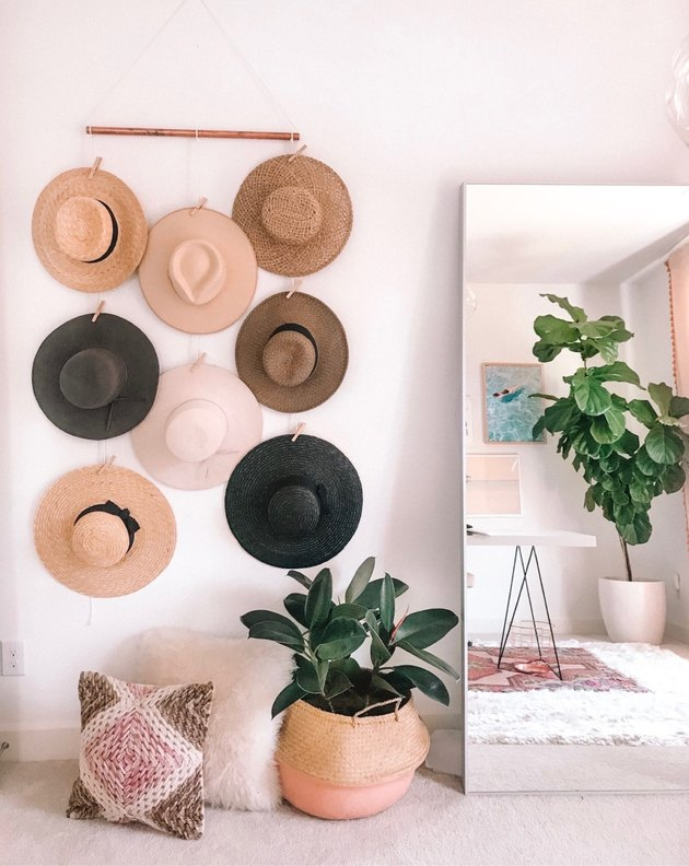 bedroom storage idea with hat wall hanging next to leaning mirror