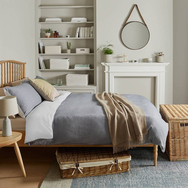 bedroom storage idea with woven containers beneath bed