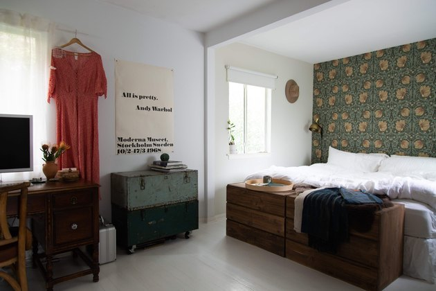 bedroom space with hanging dress and green wallpaper