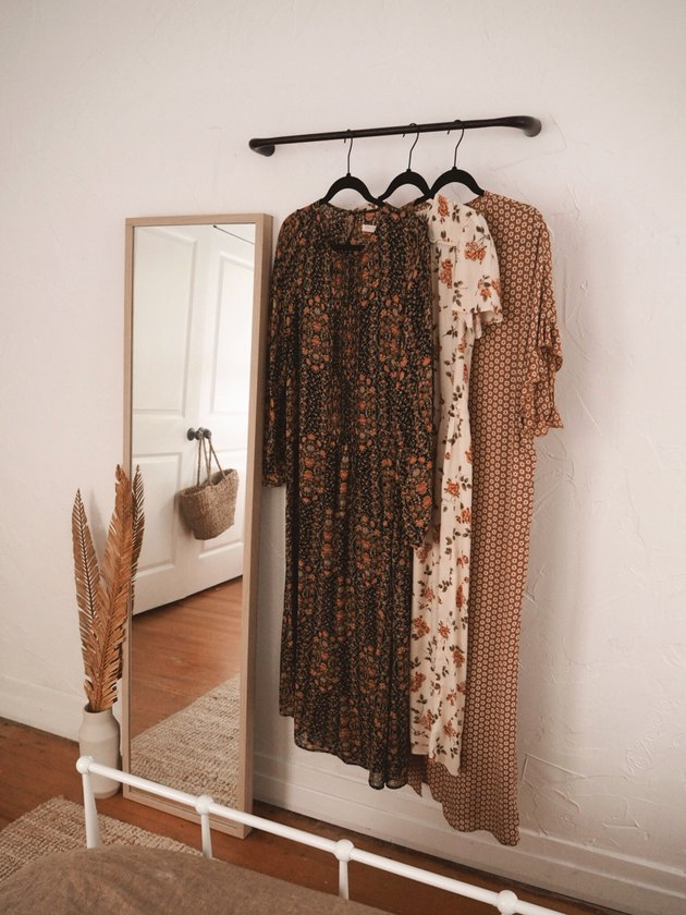 Bedroom storage ideas with towel rack hung on wall next to leaning mirror