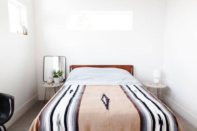 Bed with desert-style blanket and white walls
