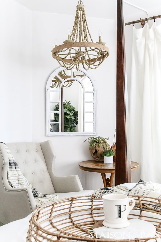 Neutral colors in French country bedroom with beaded chandelier