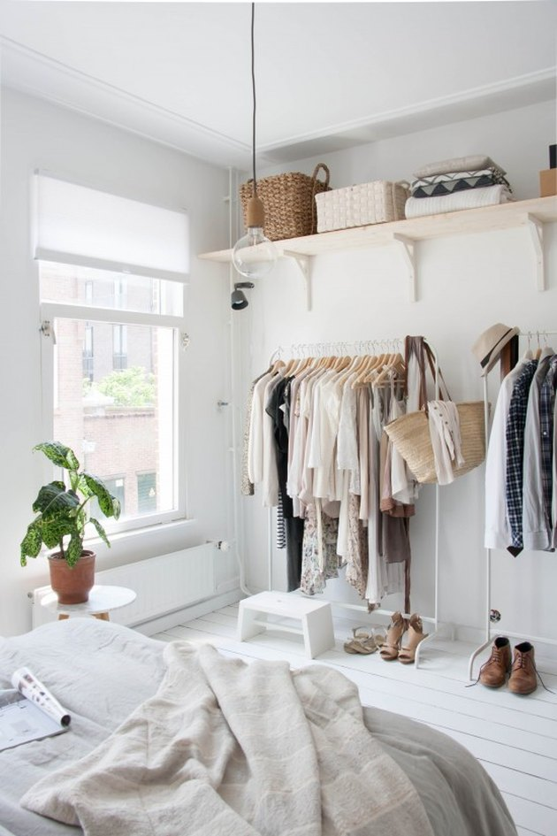 Bedroom storage idea with open shelving and freestanding clothing racks