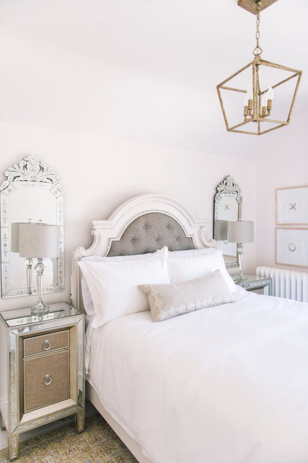 Mirrored decor in French country bedroom with pendant hanging over bed and tufted headboard