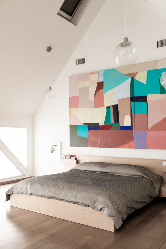 Bedroom with high ceiling and large wall art