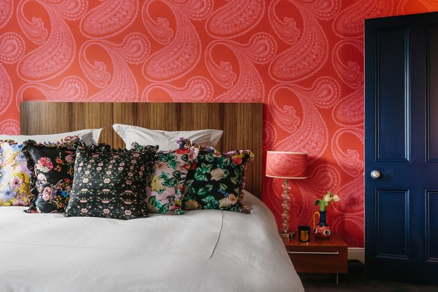 Red wallpaper on bedroom wall with blue door and wood headboard