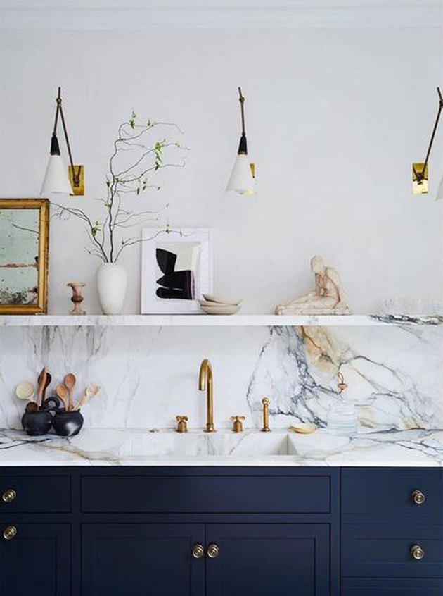 marble integrated kitchen sink with brass gooseneck kitchen faucet with blue cabinets and marble countertop