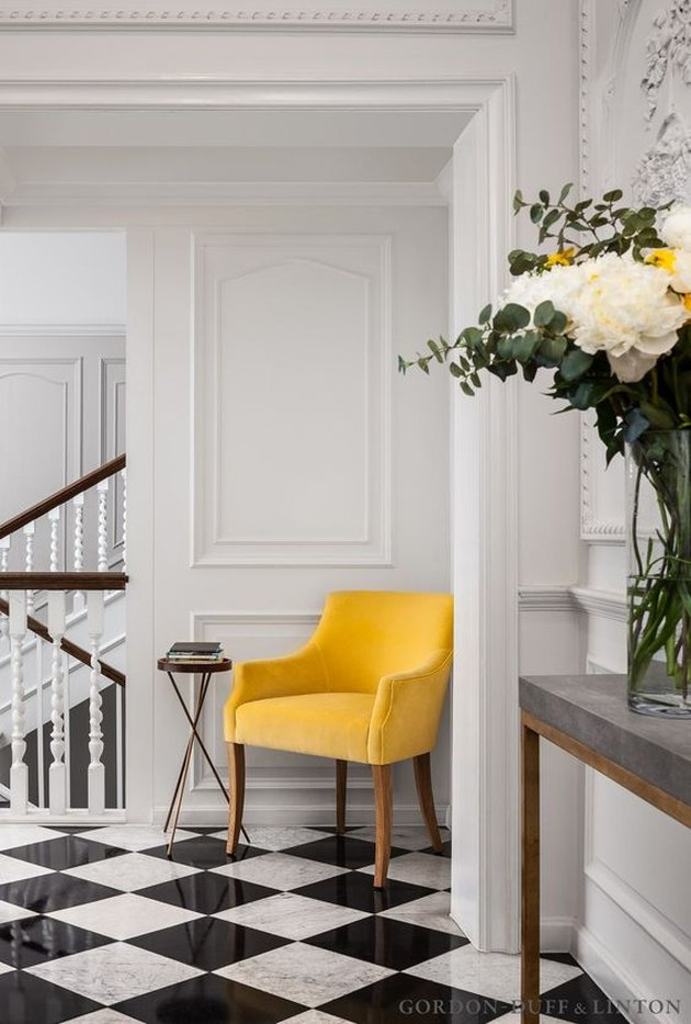 hallway with black and white floor and yellow chair in a corner