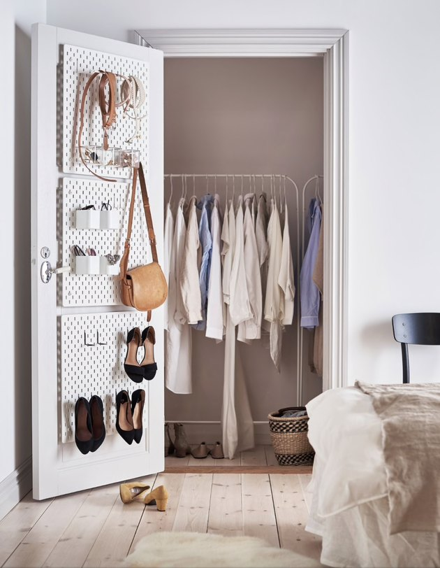 bedroom closet storage idea with shoe rack on door and clothes rack