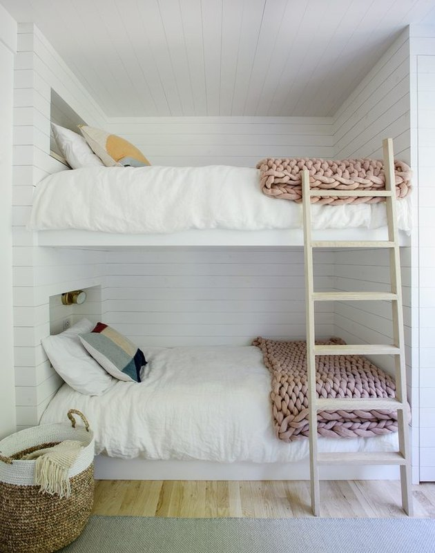 all white bedroom with shiplap walls and chunky knit bed throws