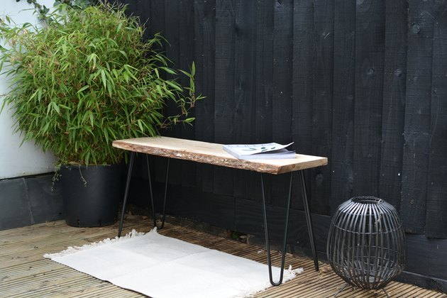 Modern outdoor bench with hairpin legs next to plant.
