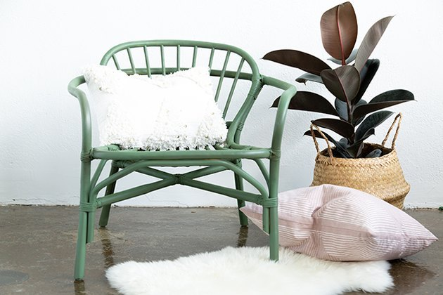 Green painted rattan chair with boho basket and plant, on sheepskin rug.