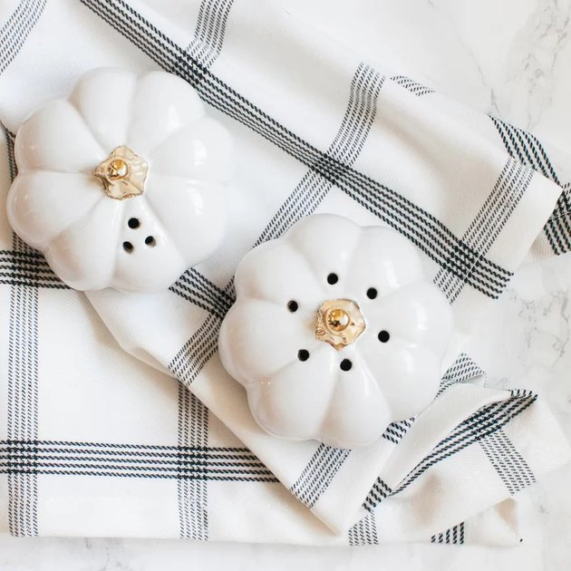 pumpkin-shaped salt and pepper shakers on plaid tablecloth
