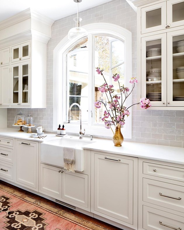 integrated kitchen appliances with farmhouse sink in white kitchen
