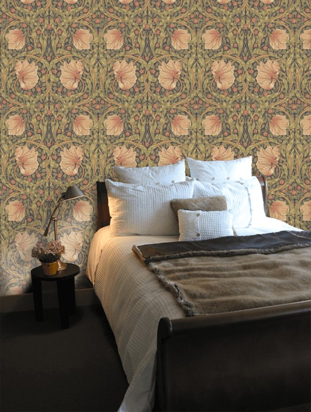 Scandinavian bedroom idea with William Morris Pimpernel Wallpaper with dark wood furniture and cozy bedding