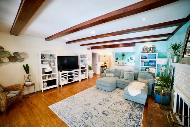 living room space with white ceiling and exposed wood beams