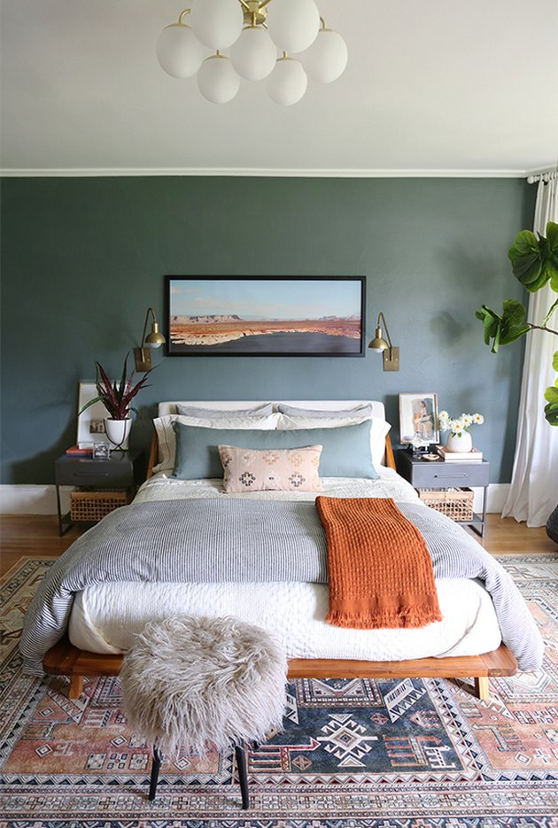 Bohemian bedroom style with green wall and faux fur stool at foot of bed