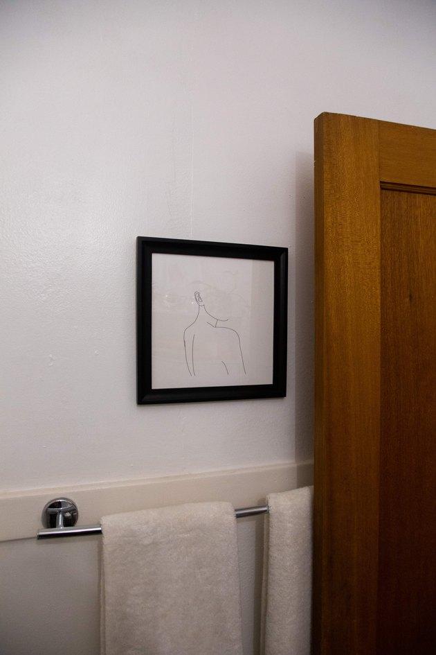 Bathroom door with art and hanging towels