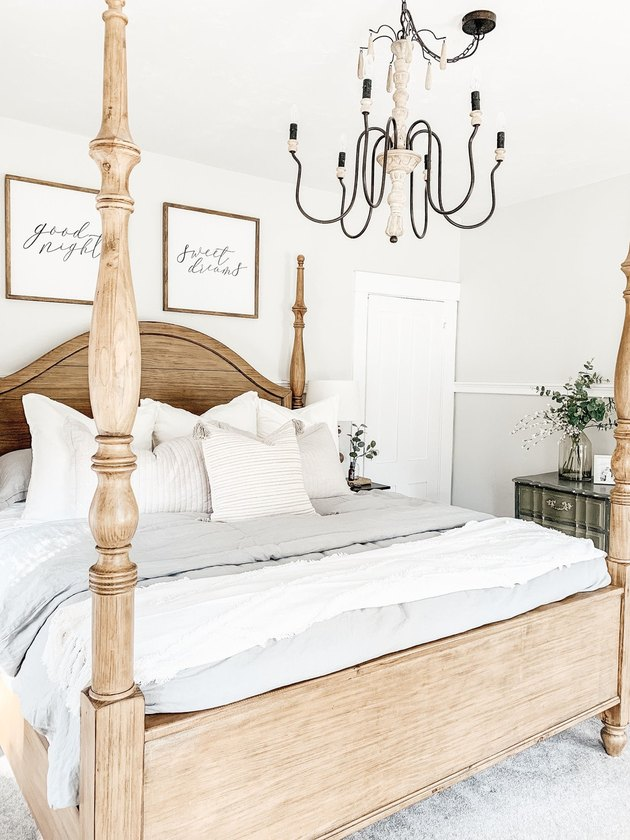 Farmhouse bedroom style with four poster wooden bed and candelabra chandelier