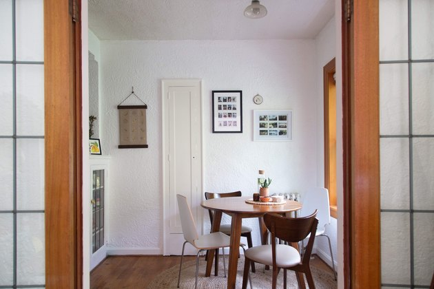small dining room idea with round table and mismatched dining chairs near window