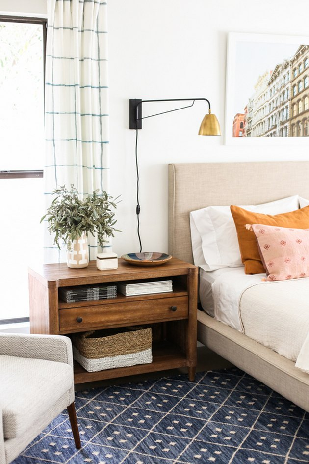 bedroom lighting idea with wall sconce above nightstand near upholstered headboard