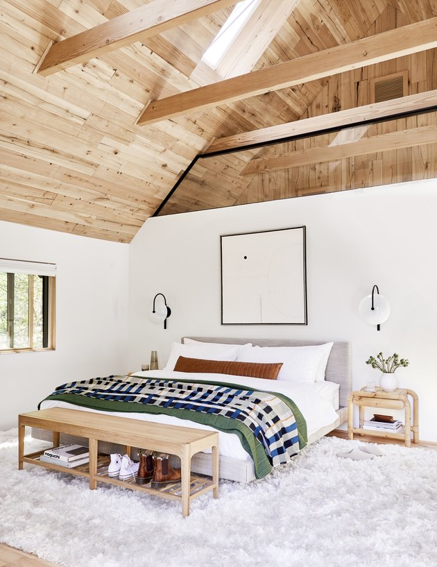 Scandinavian bedroom style with A-frame wood ceiling and wall sconces framing bed