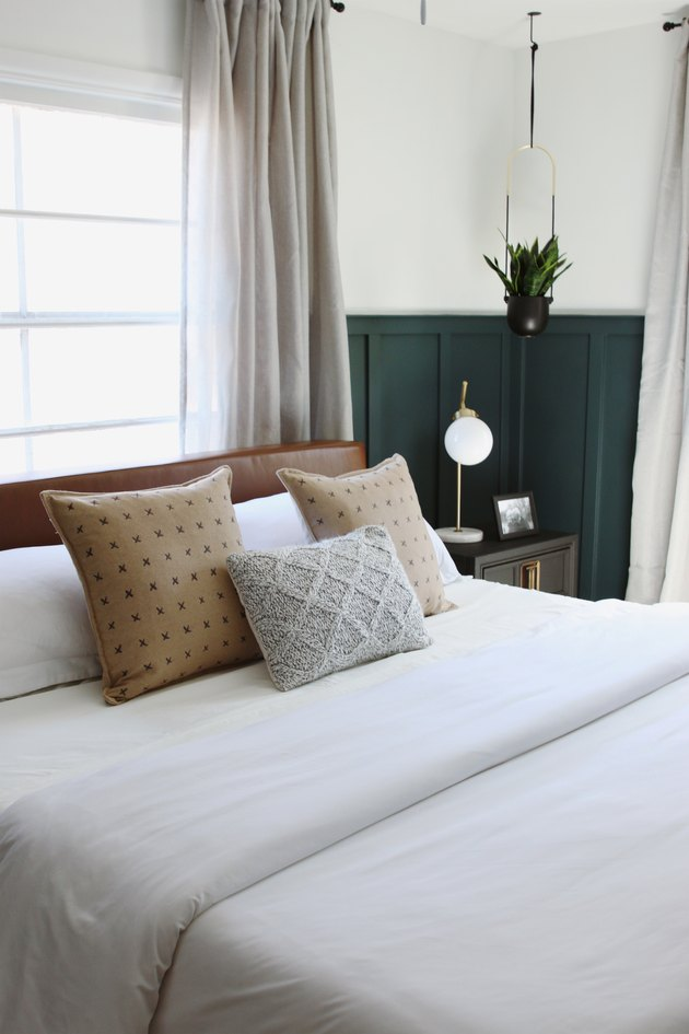 Modern bedroom style with green wainscoting and leather headboard in front of window