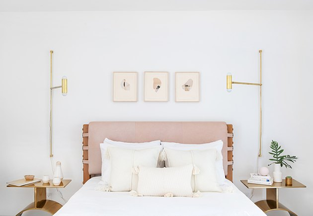guest bedroom idea with pink padded headboard and brass accents