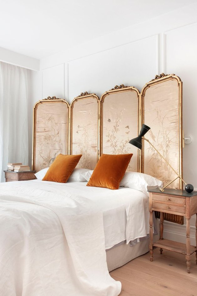 vintage bedroom style with ornate folding screen as headboard and antique nightstands with orange pillows