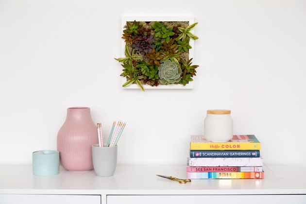 Succulent wall planter over desk with pink and blue vases, and books.