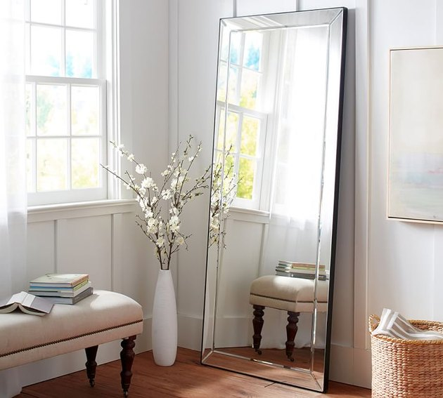 leaning frameless bedroom mirror next to accent bench and vase of flowers