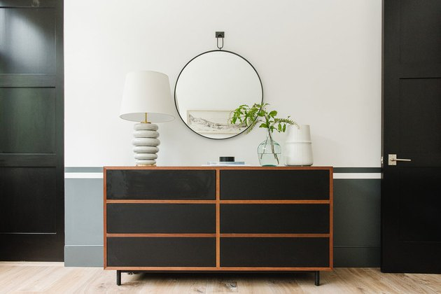 Round bedroom mirror hanging on wall above chest of drawers