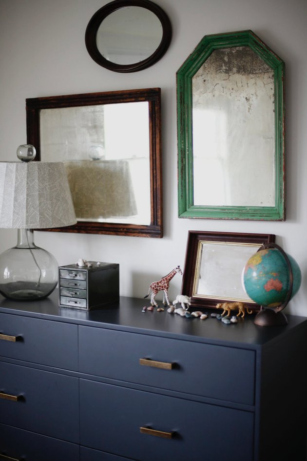 bedroom mirrors above blue dresser with table lamp and small accents