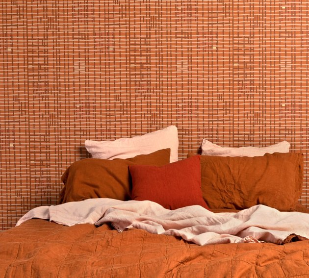 bed in front of patterned wallpaper