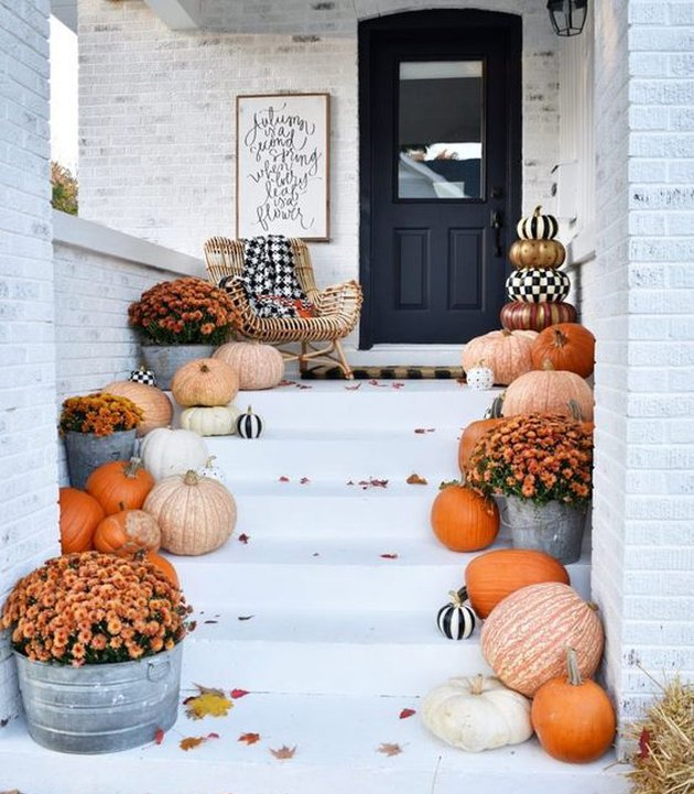 front entryway lined with pumpkins and flowers