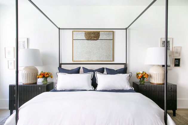 Bedroom mirror above canopy bed with dark wood nightstands