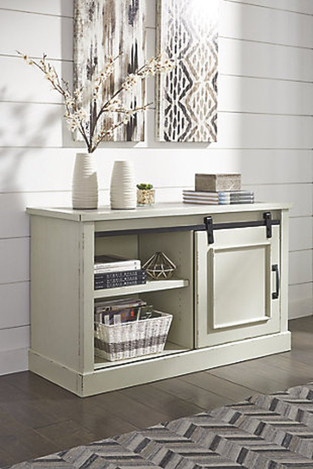 Ashley Furniture farmhouse furniture with wooden credenza for storage in front of shiplap wall