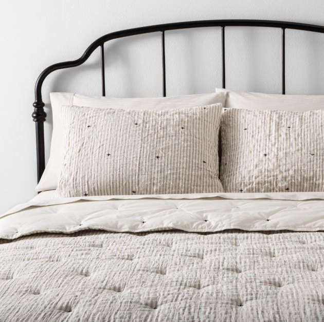 Target farmhouse decor with neutral bedding and iron headboard