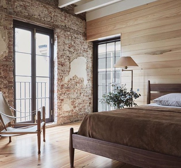 rustic bedroom with brick wall and wood paneling