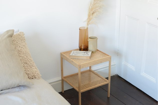 Cane bedside table in boho bedroom.