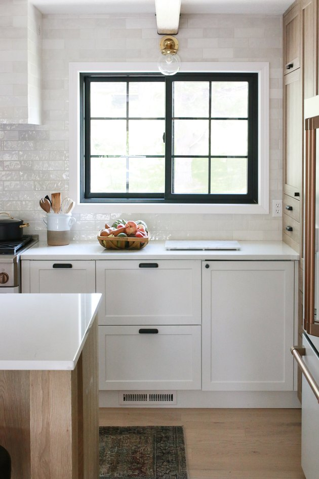 kitchen with white subway tile backsplash and black framed windows